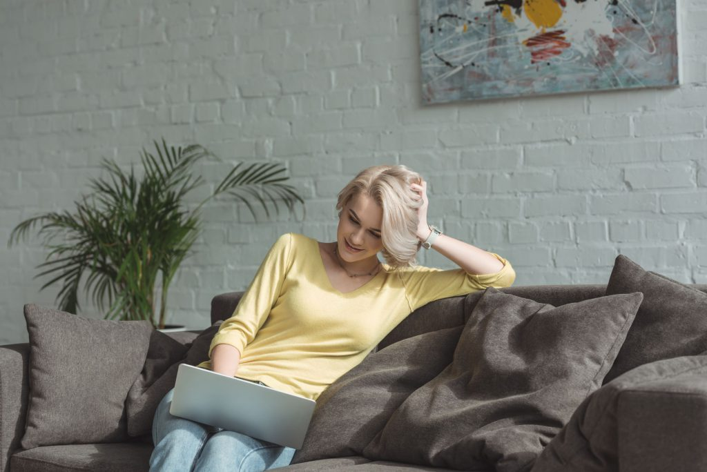 woman sitting on the sofa with a laptop