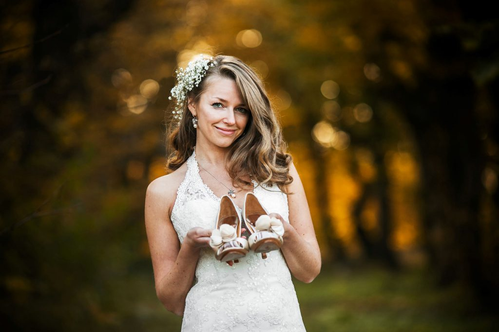 bride holding up her wedding shoes