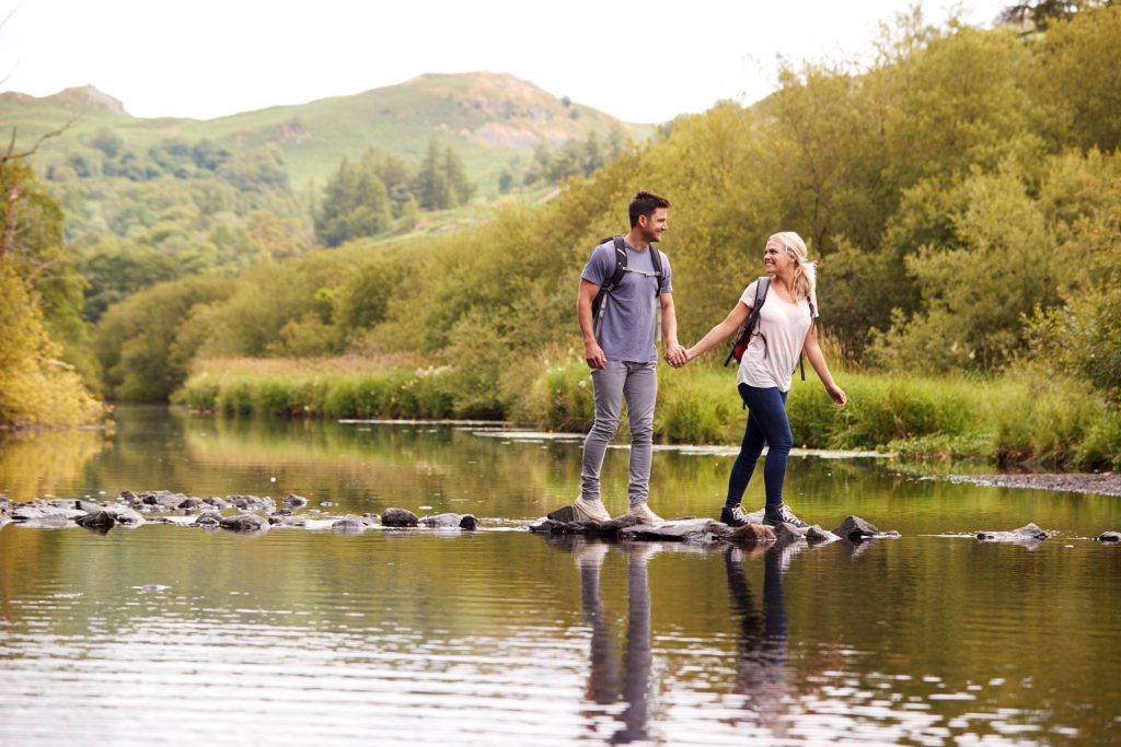 couple crossing a river in the Lake District UK