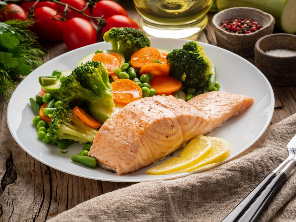 plate of food with salmon, broccoli, carrots and peas