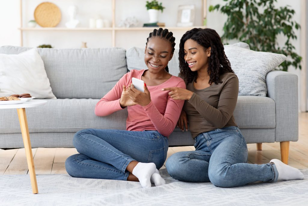 happy young women looking at a phone