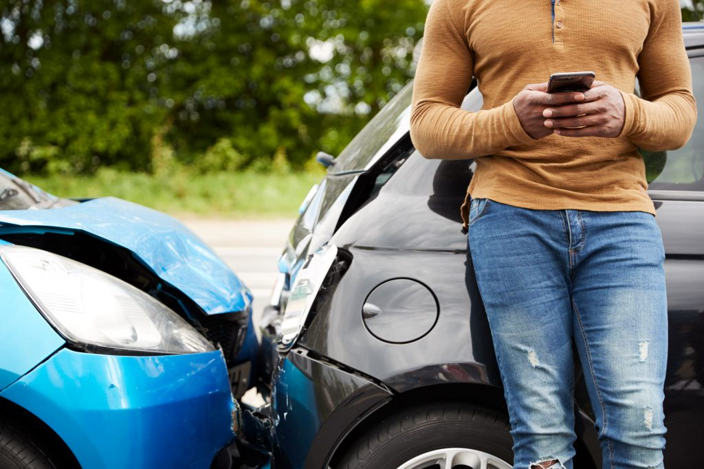 man standing by car accident calling his insurance company