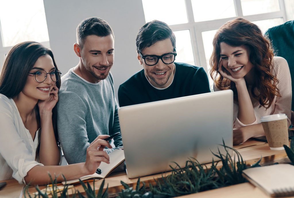 group of people looking at a laptop screen