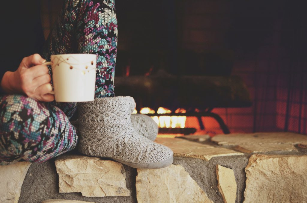 woman sat by the fire in slippers