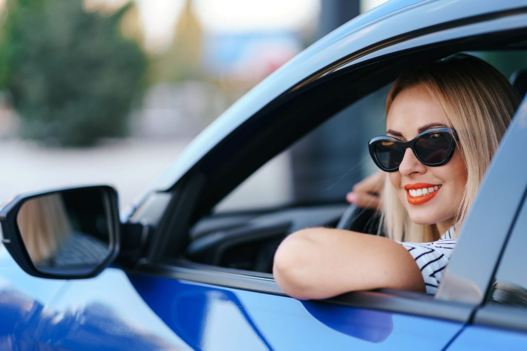 woman in sunglasses driving a car